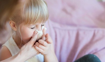Una madre ayudando a su hija a sonarse la nariz con un pañuelo de papel