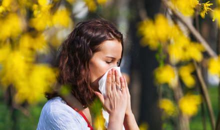 Una mujer joven estornudando en un pañuelo en un campo lleno de flores silvestres con una alta concentración de polen