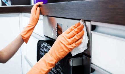 Una persona limpiando el exterior de un horno con un paño y guantes de color naranja