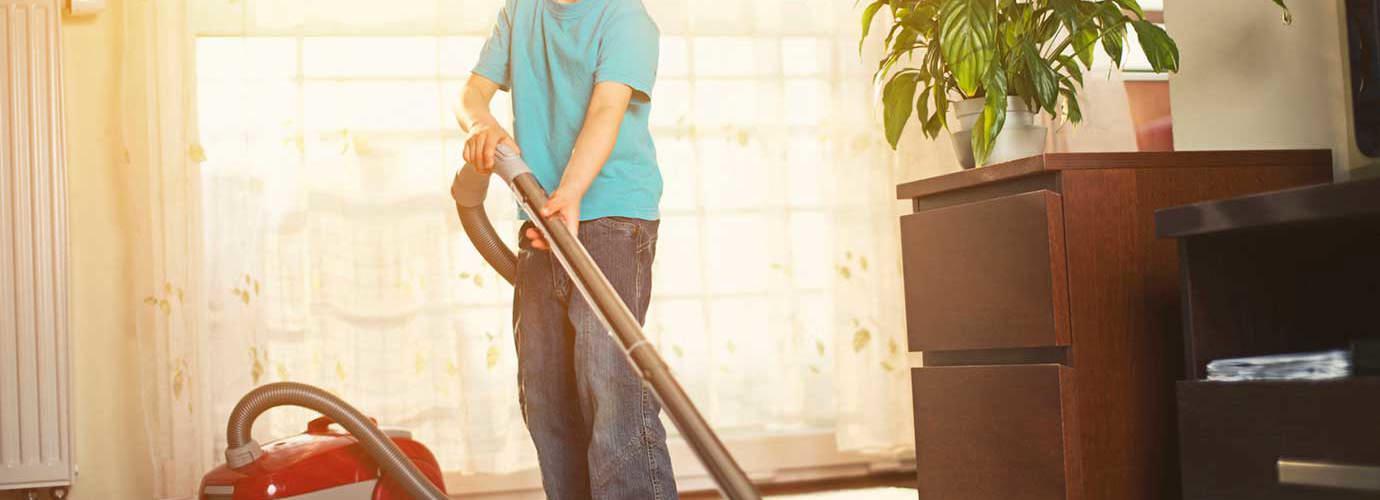 Un chico limpiando la alfombra con una aspiradora