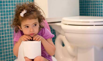 Una niña sentada en un baño con un rollo de papel higiénico en sus manos