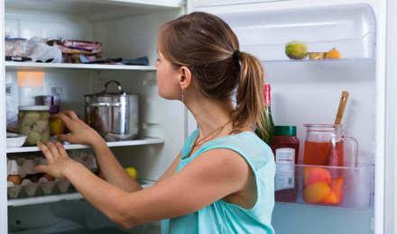 Una mujer revisando y limpiando el interior de una nevera