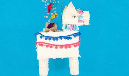 Piñata de llama blanca cubierta con papel de seda con flecos y dulces que caerán de la parte superior