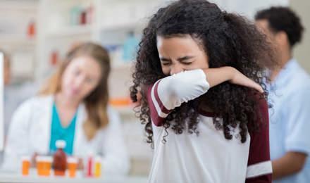 Chica estornudando en su brazo