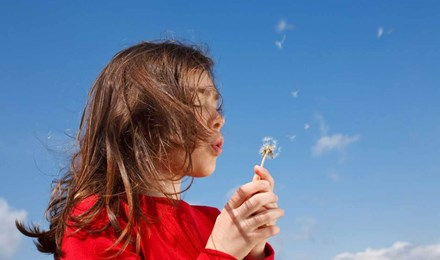 Una niña que podría necesitar algunos remedios caseros para la fiebre del heno mientras sopla un diente de león con un cielo azul de fondo