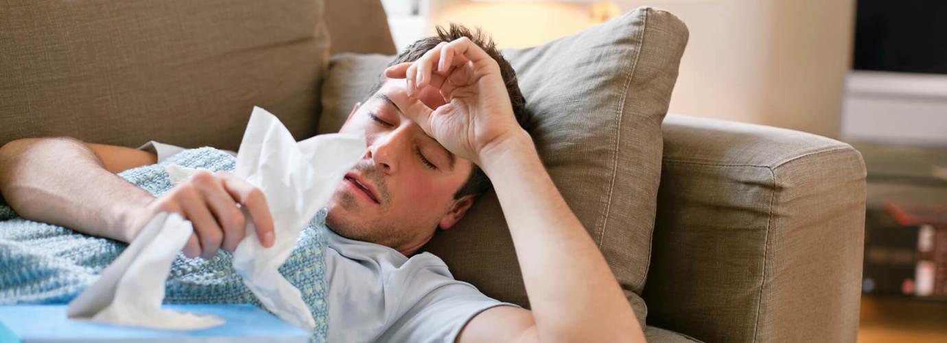 Hombre tumbado en el sofá con gripe masculina con pañuelos
