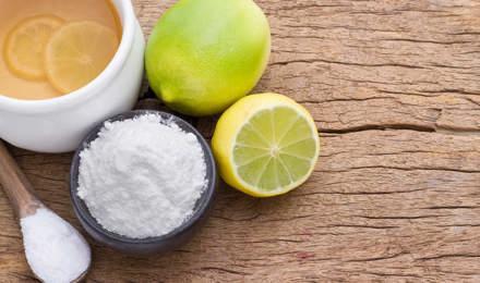 Productos de limpieza ecológicos como el limón, la lima, y el bicarbonato de sodio en una tabla de cortar de madera