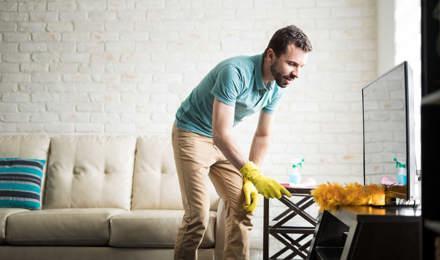 Hombre quitando el polvo de su casa con un plumero