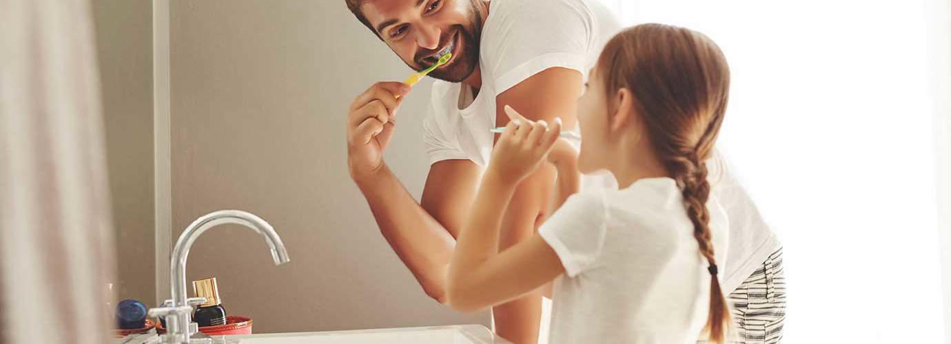 Un hombre y su hija aprendiendo a ahorrar agua mientras se cepillan los dientes juntos en un cuarto de baño