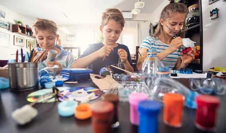 3 niños aprendiendo a reducir los residuos mediante la elaboración de manualidades de plásticos reciclables y tubos de cartón