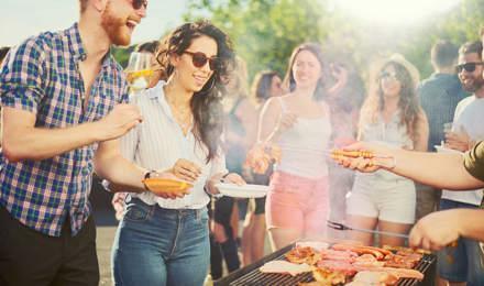 Un grupo de amigos en una fiesta barbacoa alrededor de una parrilla de barbacoa