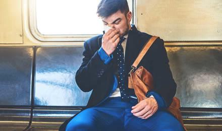 Um homem de fato sentado numa carruagem de comboio a assoar o nariz