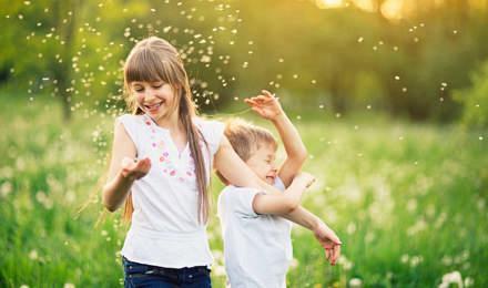 Irmão e irmã a brincarem num campo repleto de dentes-de-leão cercados por pólen