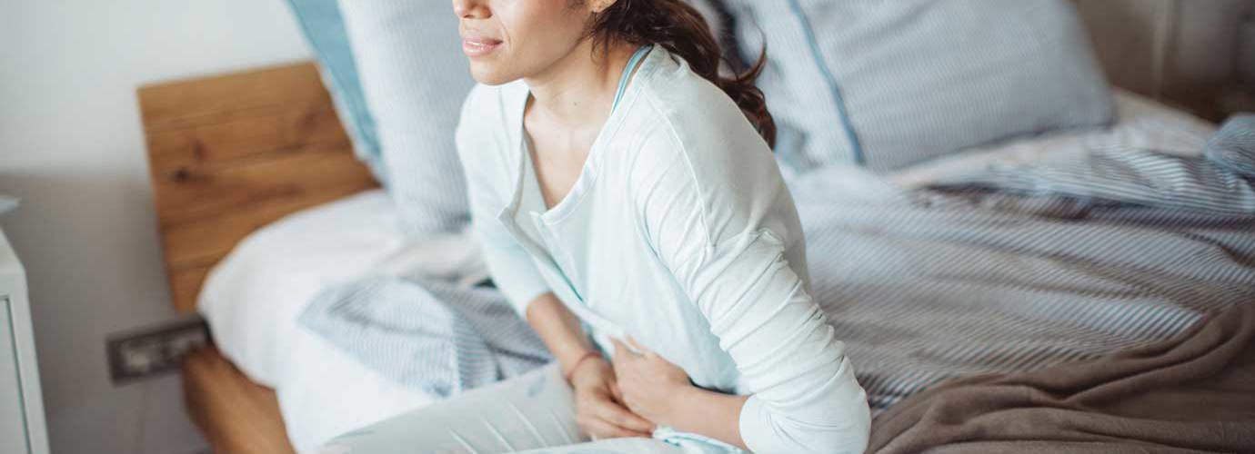 Mulher sentada na cama com dor abdominal