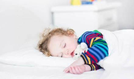Uma rapariga pequena a dormir numa cama