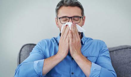 Um homem de óculos e camisa azul sentado num sofá a assoar o nariz
