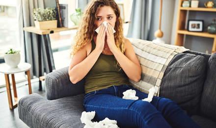 Mulher com sintomas de alergia ou constipação a assoar o nariz