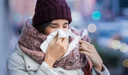 Mulher com roupas de inverno volumosas a sofrer de sintomas de sinusite e a espirrar num lenço de papel ao ar livre