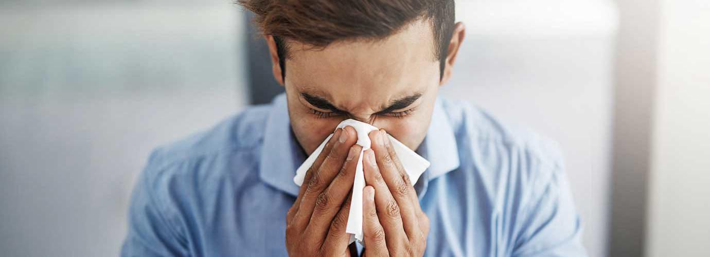 Um homem jovem a espirrar e assoar o nariz com um lenço de papel