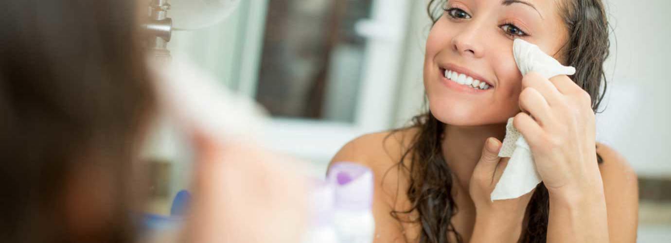Mulher a sorrir enquanto remove a maquilhagem com um lenço facial