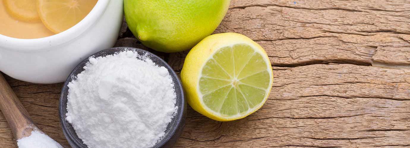Produtos de limpeza ecológicos, como limão, lima e bicarbonato de sódio numa tábua de madeira