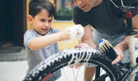 Pai e filho a limpar uma bicicleta