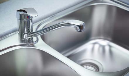 Grande plano de lavatório cromado ou de alumínio e água da torneira