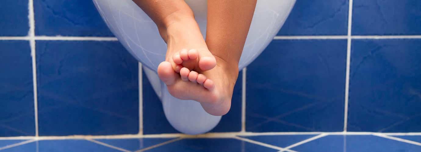 Os pés e pernas de uma criança pendurados numa sanita branca