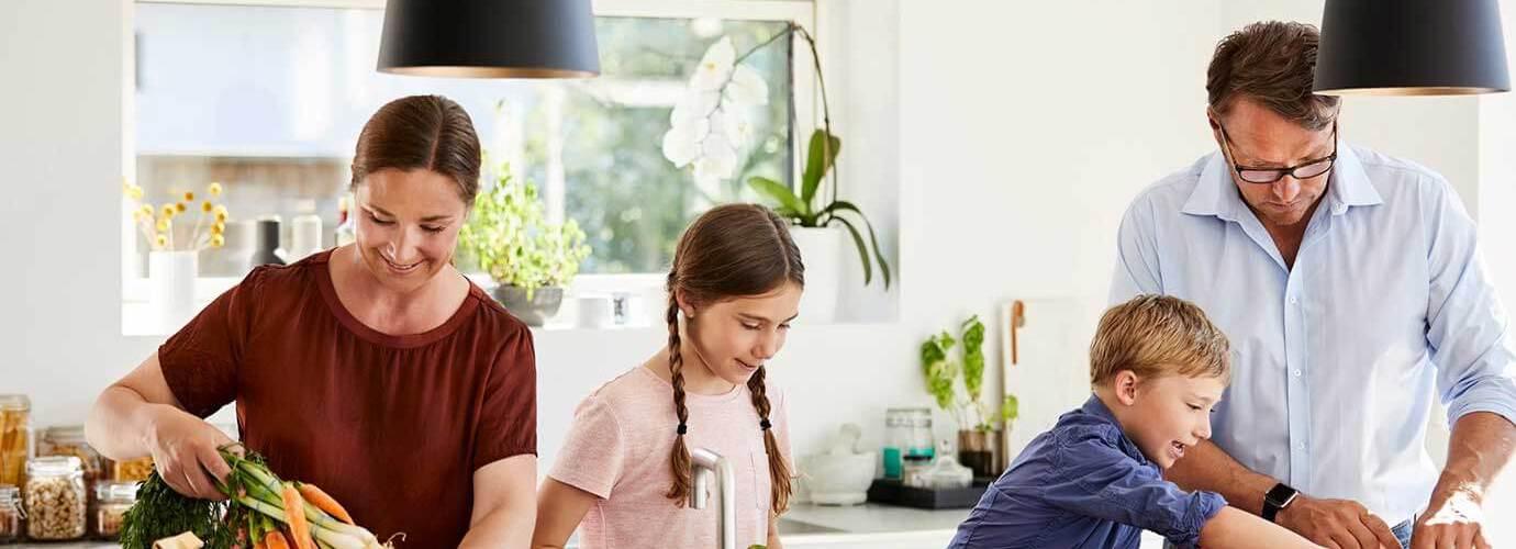 Uma mãe e um pai ensinam reciclagem às crianças enquanto tiram de embalagens recicláveis alguns alimentos na cozinha