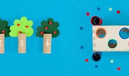 Jogos para o desenvolvimento de habilidades motoras finas feitos de tubos de papel higiénico vazios e decorados e uma caixa de lenços de papel