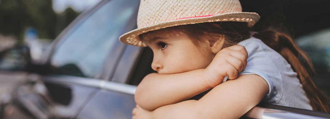 Criança enjoada num carro a usar um chapéu