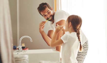 Um homem e a sua filha aprendem a economizar a água enquanto escovam os dentes juntos na casa de banho