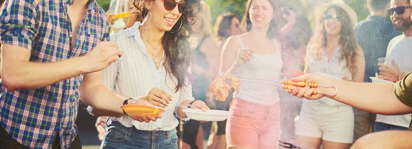 Um grupo de amigos numa festa de churrasco à volta da churrasqueira
