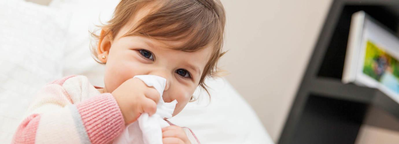 Menina a limpar o nariz com um lenço de papel