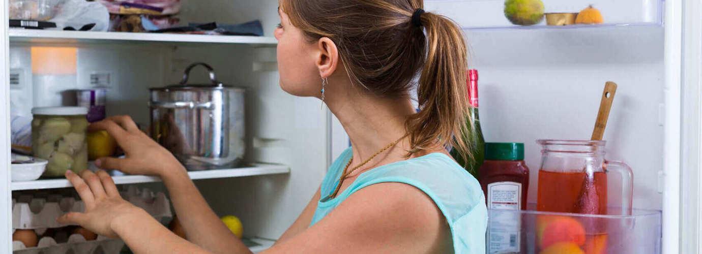 Uma mulher a verificar e limpar o interior de um frigorífico
