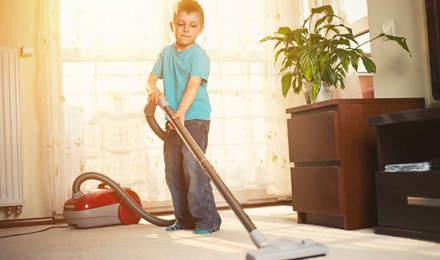 Um rapaz a limpar o tapete com um aspirador