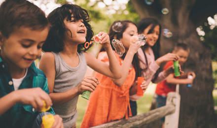 Un grupo de niños de pie sobre una valla de madera haciendo burbujas en verano