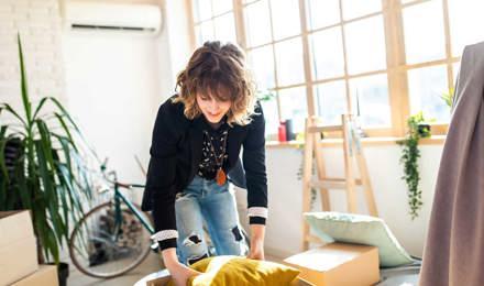 Mujer desempaquetando una caja de cartón mientras organiza la casa