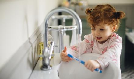 Una madre ayudando a su hija y a su hijo a lavarse las manos en la cocina